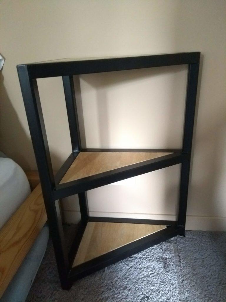 Table de chevet sur mesure en acier et bois, de forme triangulaire, pour s'adapter à la porte d'entrée près du lit.