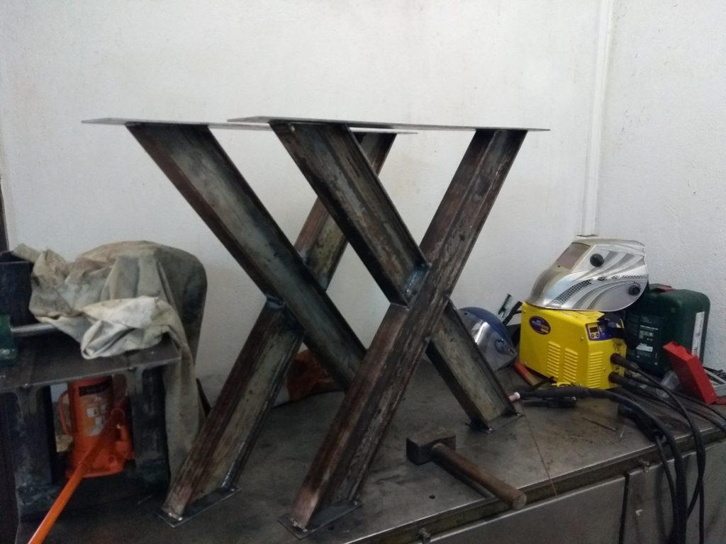 Pieds de table en acier, de design industriel, destinés à recevoir un plateau en bois massif.