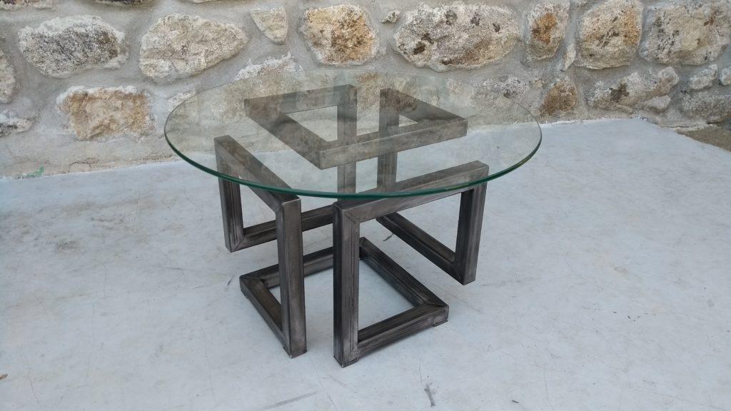Photographie d'une table basse de style industriel avec plateau en verre d'un diamètre de 60 cm.